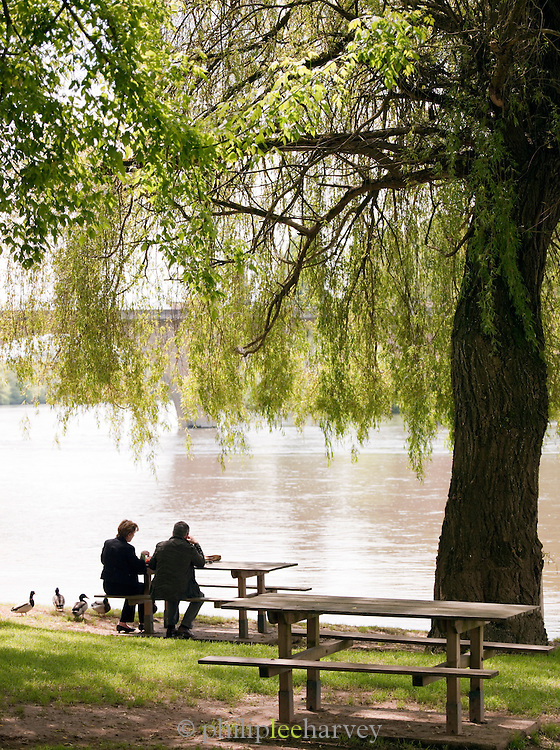 A man and woman having a picnic undera willow tree on a riverbank in Dordogne, France