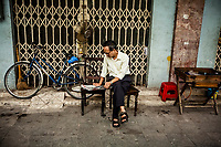 A Vietnamese man parks his bicycle and enjoys the early morning along Nha Tho Street in the Old Quarter in Hanoi, Vietnam.