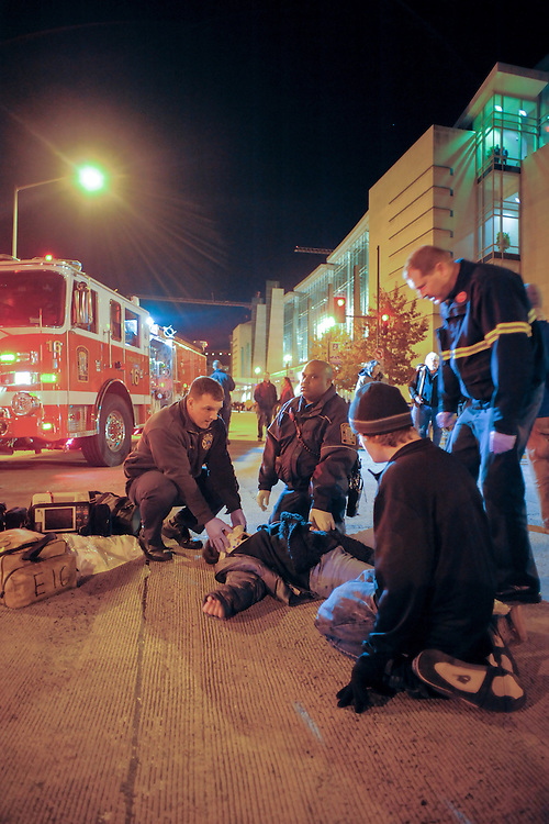 """An unidentified protester is tended to by paramedics after being hit by a vehicle that drove through a line of protesters attempting to block the street. The protesters were demonstrating against the """"Defending the American Dream"""" summit at the Washington D.C. Convention Center. An event sponsored by the Americans for Prosperity Foundation. November 04, 2011 in Northwest Washington."""