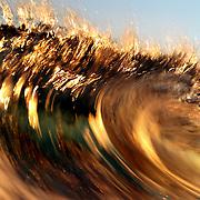 Waves break, reflecting golden light from a sunset.