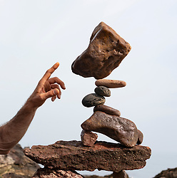 Dunbar, Scotland, UK. 20 April, 2019. Pedro Duran examines his sculpture on Eye Cave beach in Dunbar during opening day of the European Stone Stacking Championship 2019.