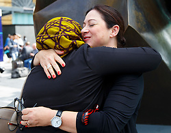 © Licensed to London News Pictures. 06/07/2015. London, UK. 7/7 survivor Gill Hicks hugging Sughra Ahmed outside King's Cross station on Monday, July 6, 2015 before walking to Tavistock Square with faith leaders to commemorate the 10th anniversary of 7/7 bombings by remembering those who lost their lives, as well as offering a message of peace and unity between people of different faiths and backgrounds. Photo credit: Tolga Akmen/LNP