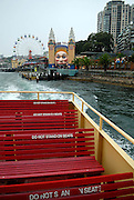 Top-deck seating on Sydney Harbour Ferry, with Luna Park in background. Sydney, Australia