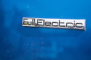 Full Electric sign on the body of a blue Citroen electric car in Wadebridge, North Cornwall, United Kingdom, a town which is aiming to become the first to be powered by renewable energy.