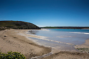 A landscape view of beautiful sandy Daymer Bay beach with clear blue sky near Trebetherick, North Cornwall, UK.