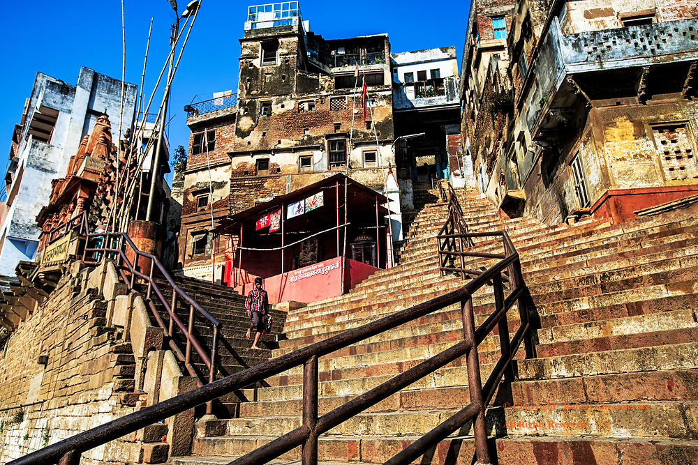 Going Up?: On a glorious sunny day, red and white stairs rise precariously high, along with rusted iron guard rails, guiding the eye up two diverging stairways into the local temples and homes, ever higher above the Ganges River, Varanasi India.