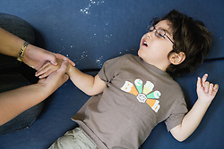Child with physical and learning disabilities lying on the floor exercising,