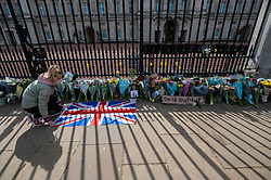 © Licensed to London News Pictures. 09/04/2021. LONDON, UK. A well wisher lays a Union flag with the flowers outside Buckingham Palace after the death of Prince Philip, aged 99, was announced.  Photo credit: Stephen Chung/LNP