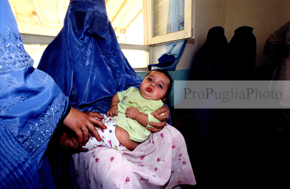 BAHARAK HOSPITAL, 28 July 2005..A  mother hold her baby in the vaccination clinic...The clinic provides vaccines against Tetanus, Polio, Thubercolosi, Measles and Diphtheria...Project supported by UNFPA