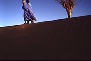 Two men chat and walk on a dune surrounding Chinguetti, Mauritania.
