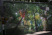 Tree print pattern hoarding designed to look natural in covering up a construction site, visually interacts with nearby trees and dappled light in central London, England, United Kingdom.