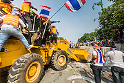 """09 DECEMBER 2013 - BANGKOK, THAILAND: Anti-government protestors use a front end loader to remove barricades blocking the roads to Government House in Bangkok. Thai Prime Minister Yingluck Shinawatra announced she would dissolve the lower house of the Parliament and call new elections in the face of ongoing anti-government protests in Bangkok. Hundreds of thousands of people flocked to Government House, the office of the Prime Minister, Monday to celebrate the collapse of the government after Yingluck made her announcement. Former Deputy Prime Minister Suthep Thaugsuban, the organizer of the protests, said the protests would continue until the """"Thaksin influence is uprooted from Thailand."""" There were no reports of violence in the protests Monday.      PHOTO BY JACK KURTZ"""