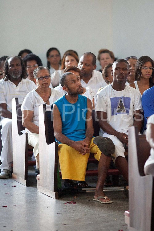 Man with one leg in the congregation, listening. Often the lines between Candomble and Catholicism are blurred. This is especially true with the Sao Lazaro event in late January in Salvador, Bahia, Brazil, the city which is known as the home of Candomble. Sao Lazaro represents healing and the sick.