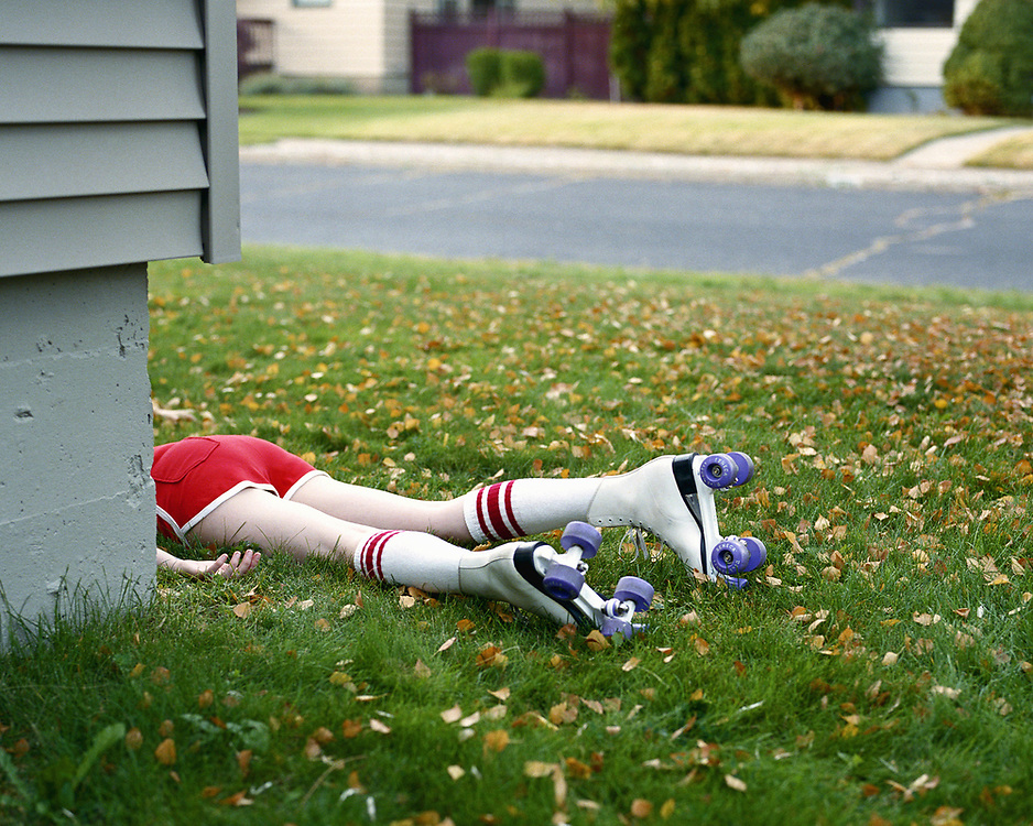 Young woman in roller skates lying in grass, low section