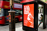 As the UKs Conornavirus pandemic lockdown continues, but with travel restrictions and social distancing rules starting to ease after three months of closures and isolation, a London bus drives past a bus stop where advertising tells the public that buses are being cleaned with antiviral disinfectant, on 9th June 2020, in London, England.