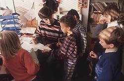 Junior school teacher and pupils in classroom,