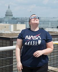 NASA employees and contractors use protective glasses to view a partial solar eclipse from NASA Headquarters Monday, Aug. 21, 2017 in Washington. A total solar eclipse swept across a narrow portion of the contiguous United States from Lincoln Beach, Oregon to Charleston, South Carolina. A partial solar eclipse was visible across the entire North American continent along with parts of South America, Africa, and Europe.  Photo Credit: (NASA/Gwen Pitman)