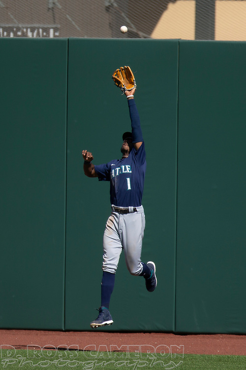 Seattle Mariners center fielder Kyle Lewis (1) leaves his feet to make the catch of a sacrifice fly by San Francisco Giants' Brandon Crawford during the sixth inning of a Major League Baseball game, Thursday, Sept. 17, 2020 in San Francisco. This is a makeup of a postponed game from Wednesday in Seattle. (AP Photo/D. Ross Cameron)