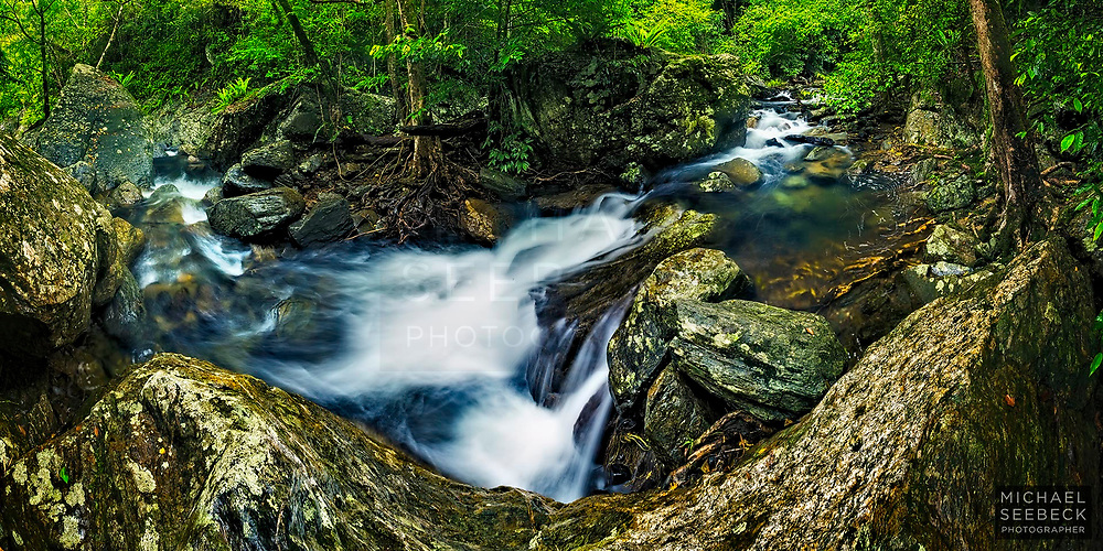A beautiful rainforest creek cascades down a mountain range in the wet season of Far North Queensland.<br /> <br /> Code: BAQT0022<br /> <br /> Panoramic Print, available in 30in (76cm) to 60in (152cm) sizes.<br /> <br /> Add to Cart to view options and pricing.