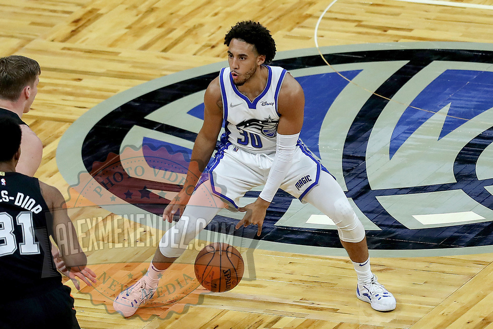 ORLANDO, FL - APRIL 12: Devin Cannady #30 of the Orlando Magic dribbles the ball in front of Luka Samanic #19 of the San Antonio Spurs at Amway Center on April 12, 2021 in Orlando, Florida. NOTE TO USER: User expressly acknowledges and agrees that, by downloading and or using this photograph, User is consenting to the terms and conditions of the Getty Images License Agreement. (Photo by Alex Menendez/Getty Images)*** Local Caption *** Devin Cannady; Luka Samanic