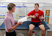 Director of the UVA SPEED Clinic Max Prokopy, left, talks with Matt Clay about his stretches and workouts during a visit to the clinic in Charlottesville, VA. Photo/Andrew Shurtleff