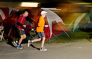 Augusta, New Jersey - Two men run at night past tents set up along the course during the 3 Days at the Fair races at Sussex County Fairgrounds on May 12, 2012.