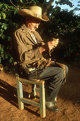 Elderly man sitting on chair rolling a cigar from tobacco leaves at Vinales; Cuba,