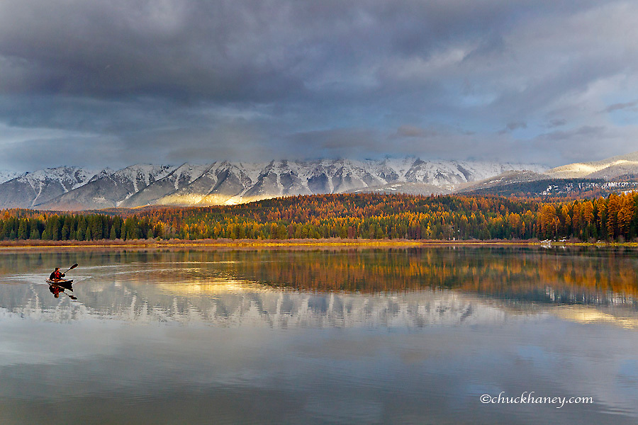 Kayaking on a stormy autumn evening in Rainy Lake with the Swan Mountain Range in the Lolo National Forest, Montana, USA model released