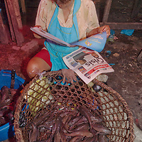 A bored merchant reads a tabloid as she waits for customers to buy her fish at an outdoor market in upper Belem, a crowded neighborhood in Iquitos, Peru.