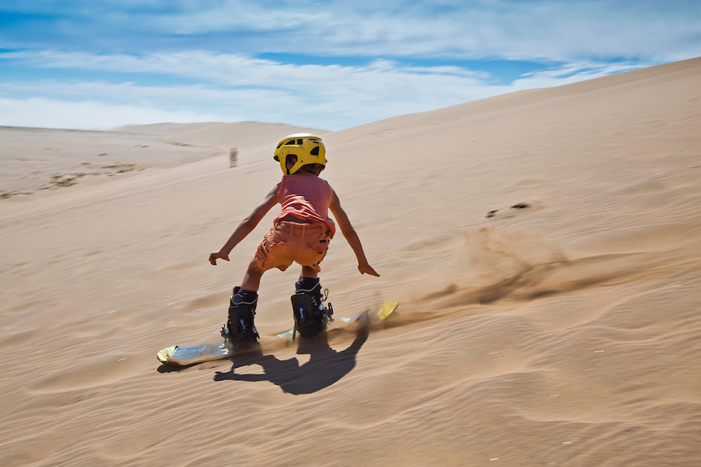 A young boy tries sand boarding just outside of Swakopmund on the dunes along the B2 road.