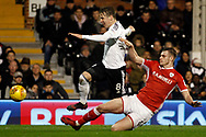 Stefan Johansen of Fulham (L) evades a challenge from Liam Lindsay of Barnsley (R). EFL Skybet championship match, Fulham v Barnsley at Craven Cottage in London on Saturday 23rd December 2017<br /> pic by Steffan Bowen, Andrew Orchard sports photography.