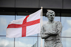 © Licensed to London News Pictures. 26/04/2018. LONDON, UK.  The England flag flies behind the statue of Bobby Moore outside Wembley Stadium.  It is reported that the Football Association (FA) has received a bid of GBP800m from Shahid Khan, owner of Fulham FC and the Jacksonville Jaguars NFL franchise, to purchase the stadium.  If the bid is successful, the FA will retain its organisational base at the stadium, but will open the way for the creation of the first NFL franchise located out of the United States.  Photo credit: Stephen Chung/LNP