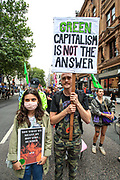 People hold banners, placards and some of them wave flags during an Extinction Rebellion climate protest near Covent Garden in central London on Monday, Aug 23, 2021. This is a two week planned action against new fossil fuel investments. Protestors are demanding that Government halt all new investment in fossil fuels. (VX Photo/ Vudi Xhymshiti)