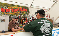 Keith Hall mans the Laconia Rotary Booth on Lakeside Avenue as Mark Jaquin of Oswego, NY purchases his chance to win the Harley Davidson Heritage Softtail Classic which will drawn on Sunday.  (Karen Bobotas/for the Laconia Daily Sun)