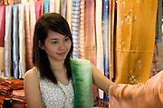 Southeast Asia, Thailand, Bangkok. The Sunday market. Young woman selling fabric in a material shop