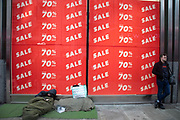 Homeless man on Oxford Street walk in a sleeping bag by a large scale January sale signs in red and white for major high street clothing retail shops on 7th January 2019 in London, United Kingdom. Its time for the Winter sales, and most shops are advertising big reductions in prices. Bargains are available and the shopping streets are busy. Oxford Street is a major road in the West End of London. It is Europe's busiest shopping street, with around half a million daily visitors, and has approximately 300 shops. (photo by Mike Kemp/In Pictures via Getty Images)