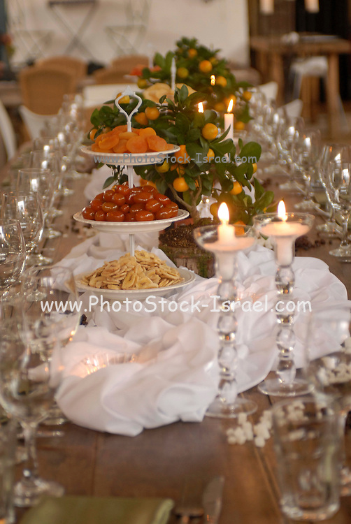 """Table set with dried fruit and nuts for the Jewish celebration of Tu Bishvat the """"New Year of the Trees"""" Customs include planting trees and eating dried fruits and nuts,"""