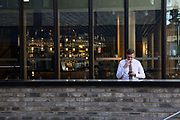 A businessman smokes a cigarette while using his mobile phone on 06th June 2017 in London, United Kingdom. From the series Our Small World, an observation of our mobile phone obsessions