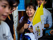 19 NOVEMBER 2017 - HWAMBI, YANGON REGION, MYANMAR: A woman with a papal flag she bought at Sacred Heart's Catholic Church in Hwambi, about 90 minutes north of Yangon. Catholics in Myanmar are preparing for the visit of Pope Francis. He is coming to the Buddhist majority country November 27-30. There about 500,000 Catholics in Myanmar, about 1% of the population. Catholicism was originally brought to what is now Myanmar more than 500 years ago by Portuguese missionaries and traders.    PHOTO BY JACK KURTZ
