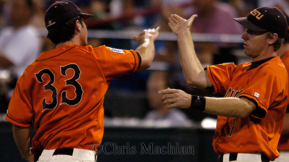 06/19/2006 Oregon State starter Mike Stutes (No. 33)  is greeted by Casey Priseman after finishing the first inning during game ten of the College World Series in Omaha Nebraska Tuesday evening..(photo by Chris Machian/Prairie Pixel Group)