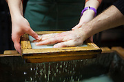 A person presses their hand onto a pulp mould to make paper with a hand print at the historic Paper Mill in Duszniki-Zdroj, Poland.