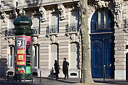 Couple walk past obelisk advertising theatre productions in Parisian street, Boulevard St Germain, Latin Quarter, France