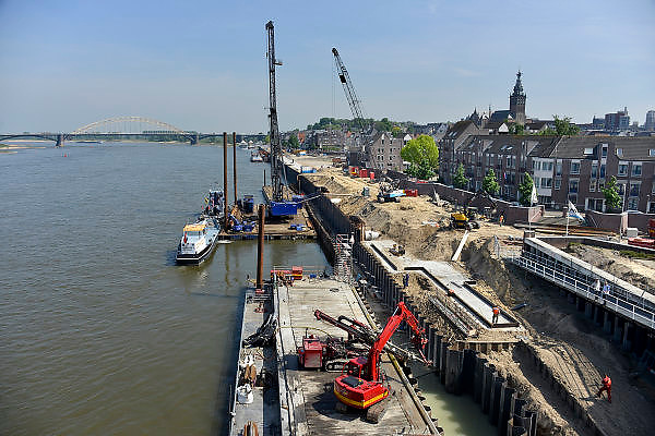 Nederland, Nijmegen, 5-5-2014Aan de Waalkade wordt gewerkt aan de vervanging van de damwand. De waterkering werd ondergraven door wegspoelend zand en raakte uit positie en dus instabiel. Reef Infra en Colijn Aannemersbedrijf vervangen de 12 meter lange stalen damwandplanken door damwandplaten van 26 meter lang. Ook wordt de verankering vervangen. De nieuwe damwandconstructie is berekend op de zware belasting door steeds grotere schepen die over de rivier de Waal varen, en moet langer meegaan als de oude uit 1980.Boren, boortechniek, verankerenFoto: Flip Franssen/Hollandse Hoogte