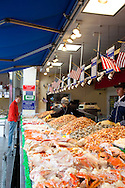 """The Maine Avenue Fish Market of Washington, D.C., also known as """"the Wharf"""" or """"the Fish Wharf"""", is one of the few surviving open air seafood markets on the east coast. In operation since 1805, it is the oldest continuously operating fish market in the United States.  The Maine Avenue Market was relocated in the 1960s, within a few blocks of its original location on the Washington Channel...Located on the Southwest waterfront under the shadow of Interstate 395, it stands as a cultural relic popular with locals but unknown to many of the tourists who flock to the monuments and museums just five blocks north. There are over ten stores, each with a specialty. The Maine Avenue Fish Market is open each day of the week, but the largest selection of fish is on display Friday evening through Sunday."""