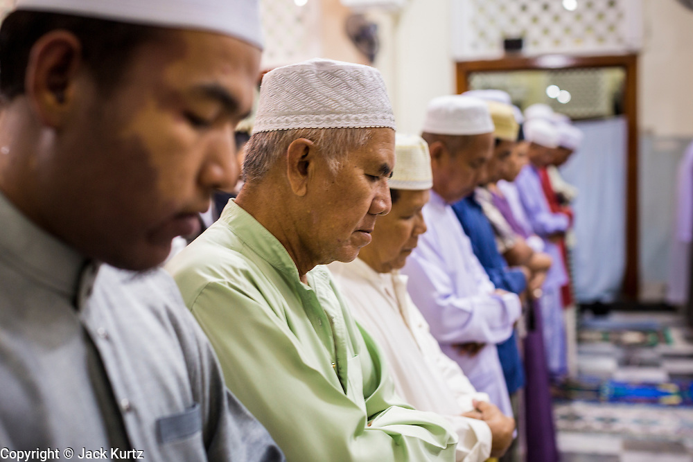 09 JULY 2013 - PATTANI, PATTANI, THAILAND:  Muslim men pray in Pattani Central Mosque in Pattani, Thailand, Tuesday night on the first night of Ramadan. Ramadan is the ninth month of the Islamic calendar, and the month in which Muslims believe the Quran was revealed. Muslims believe that the Quran was sent down during this month, thus being prepared for gradual revelation by Jibraeel (Gabriel) to the Prophet Muhammad. The month is spent by Muslims fasting during the daylight hours from dawn to sunset. Fasting during the month of Ramadan is one of the Five Pillars of Islam.   PHOTO BY JACK KURTZ