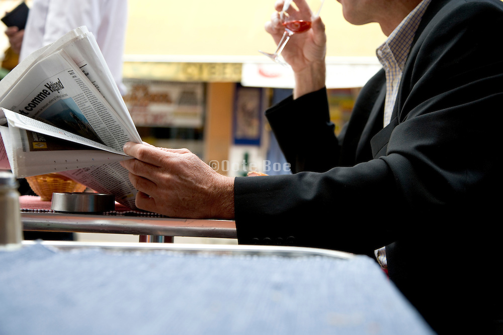 businessman reading a newspaper while taking a lunch break France