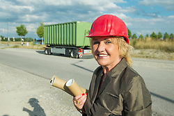 Businesswoman wearing safety helmet, carrying construction plans