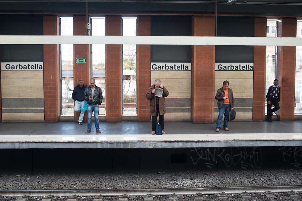 Five men wait for the metro at the Garbatella station in Rome, Italy