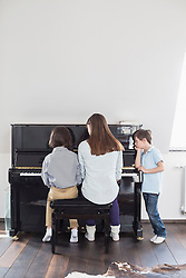 Mother and daughter playing piano while brother is listening