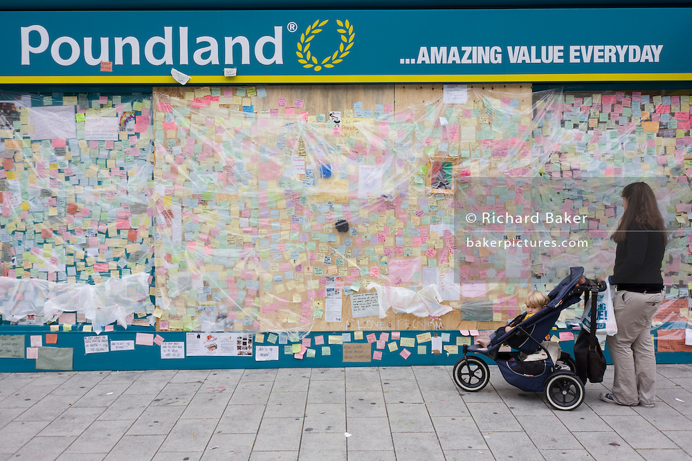 A local Peckham mother stops to read the spontaneous messages of love on the Poundland peace wall after the London riots. In response to the violence and destruction that took place the week before, communities reacted with anger in a way rarely seen in a large UK city these days. The messages vary in their sentiment but generally echo a sense of disgust at the looting and rioting with brief notes of co-operation, advice and communal encouragement. Walls like these have sprung up in other locations where destruction was widespread and locals lost their convenience stores, sports shops and even homes.